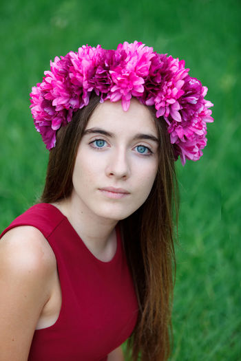 Close-up portrait of beautiful woman with pink flower