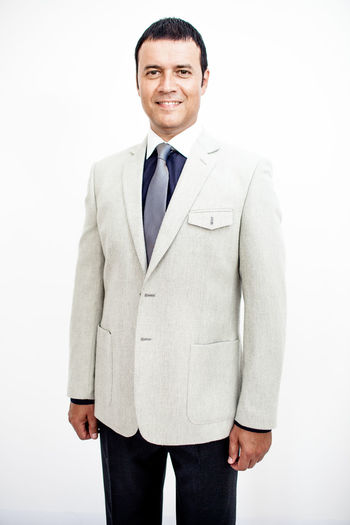 Man in classic suit on the white background. Studio shot. Business Business Stories Adult Business Business Finance And Industry Businessman Clothing Formalwear Front View Happiness Indoors  Looking At Camera Males  Men Menswear One Person Portrait Smiling Standing Studio Shot Three Quarter Length Well-dressed White White Background Young Adult