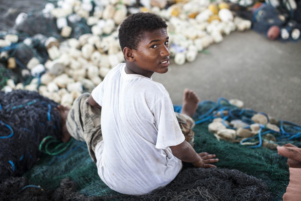 Portrait of teenage boy sitting on fishing net