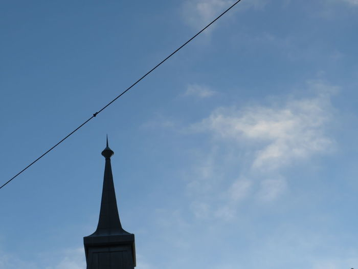 Low angle view of cross and building against sky
