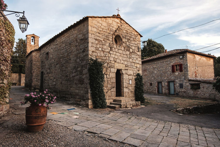 Old Town Tuscany Architecture Building Building Exterior Built Structure City Cloud - Sky Flower Footpath History House Italy Nature No People Outdoors Paving Stone Plant Potted Plant Religion Residential District Stone Wall Street The Past Wall
