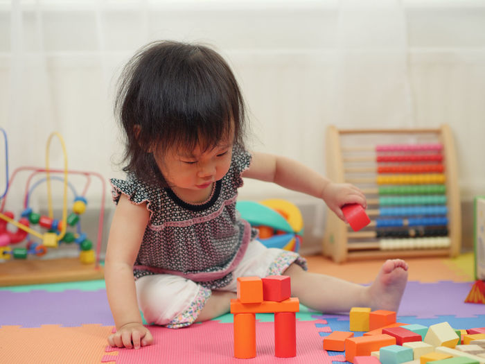 Girl Playing With Colorful Toy Blocks At Home
