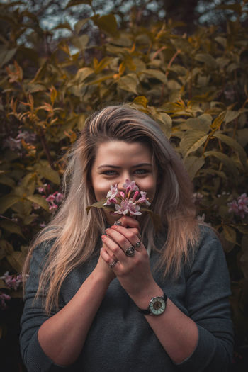 Portrait of smiling young woman holding flowers against tree