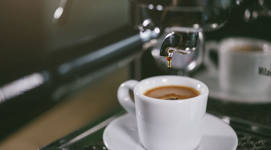 Close-up of machinery dripping coffee in cup on table