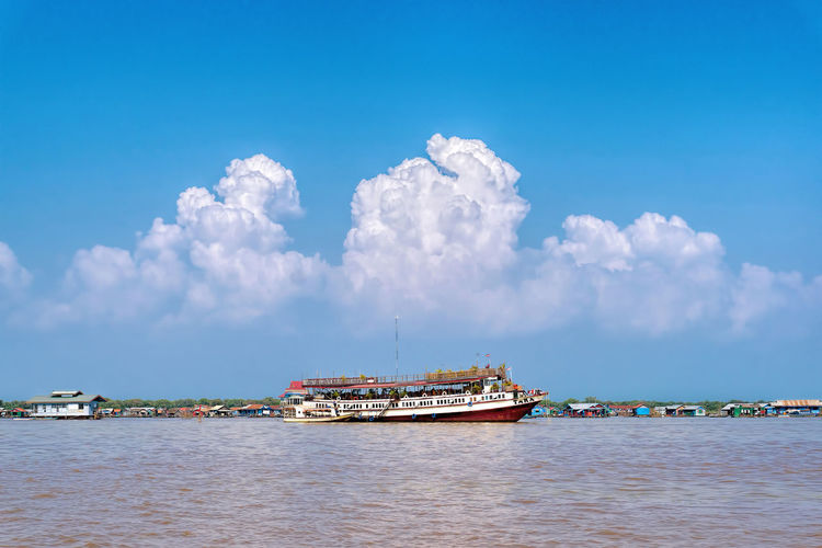 Passenger craft sailing in river against sky