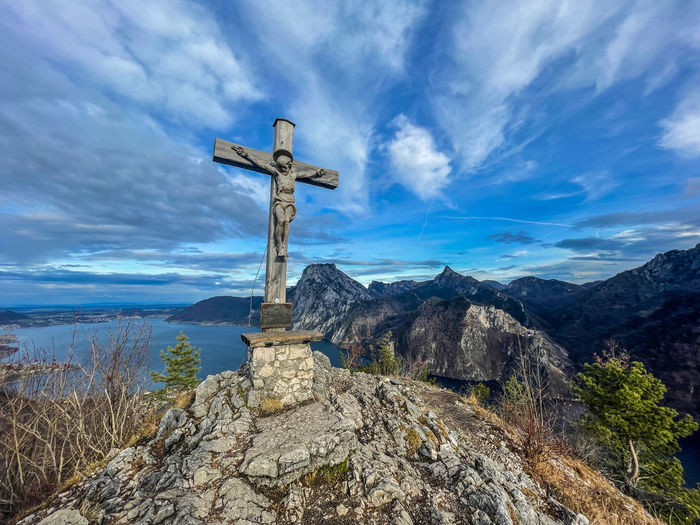 Cross on mountain against sky