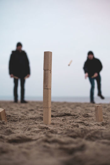 Men aiming for stack of blocks at shore of beach