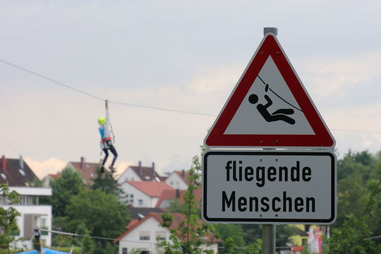 Close-up of road sign against sky