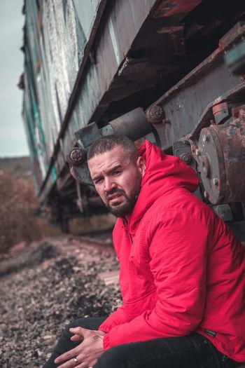 Portrait of man sitting against train