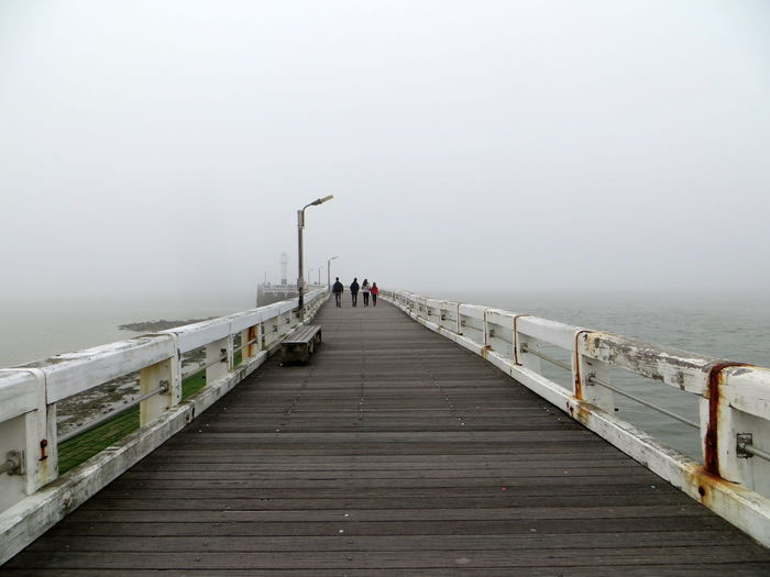 People walking on pier over sea during foggy weather