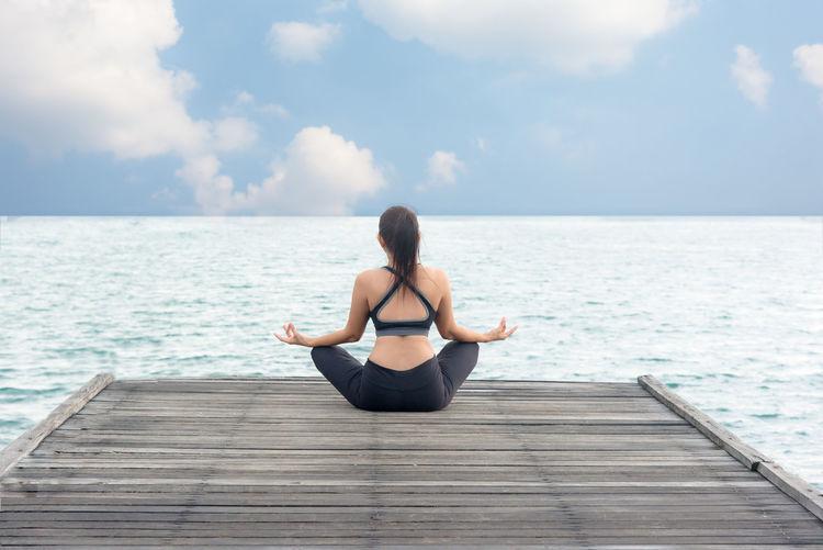 Full length of woman sitting on sea against sky