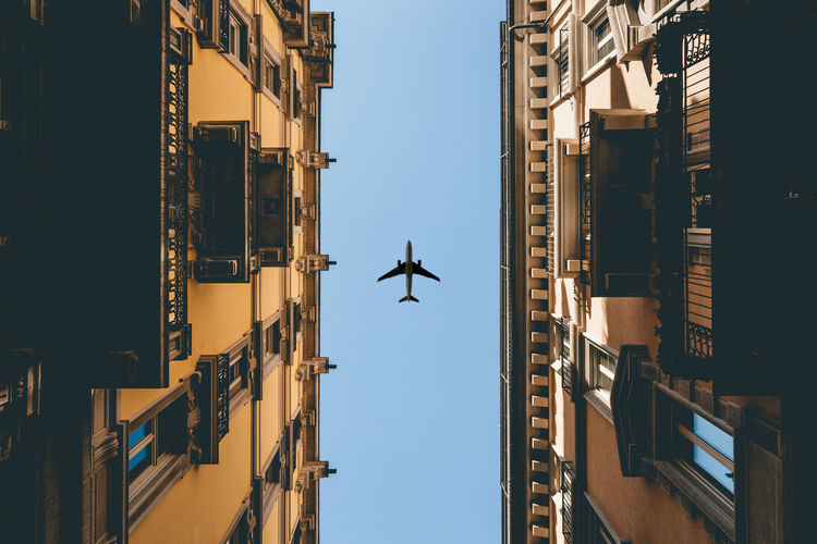 Airplane flying over buildings against clear sky