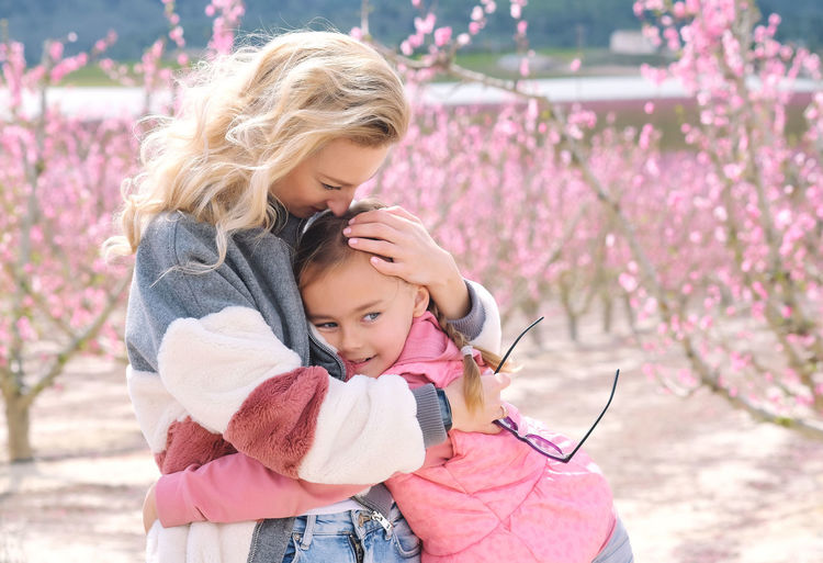 Cute girl embracing mother against cherry trees