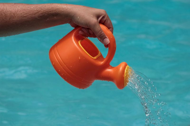 Summer Orange Color Pouring Water Pouring Human Hand Hand Water Human Body Part One Person Pool Swimming Pool Close-up Motion Outdoors Splashing Holding Turquoise Colored Blue