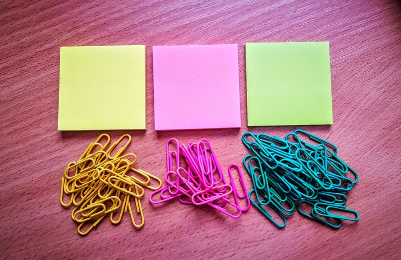 Close-up of multi colored papers and paper clips on table