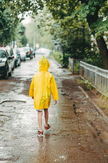 boy in a yellow raincoat comes out in the rain. child alone walks in the rain.