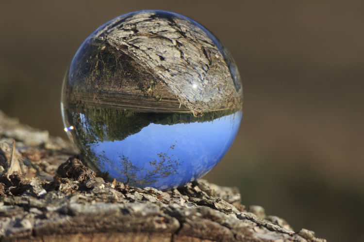 Close-up of crystal ball against blue water