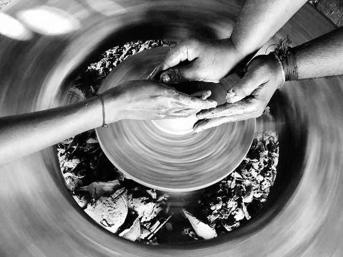Cropped hands of people making pottery
