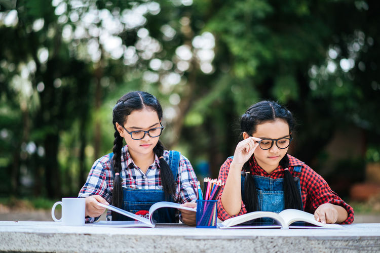Activity Adult Book Communication Education Eyeglasses  Focus On Foreground Friendship Front View Glasses Hair Learning Leisure Activity Outdoors Publication Reading Sitting Studying Togetherness Two People Wireless Technology Young Adult Young Women