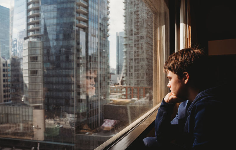 Portrait of young man looking through window