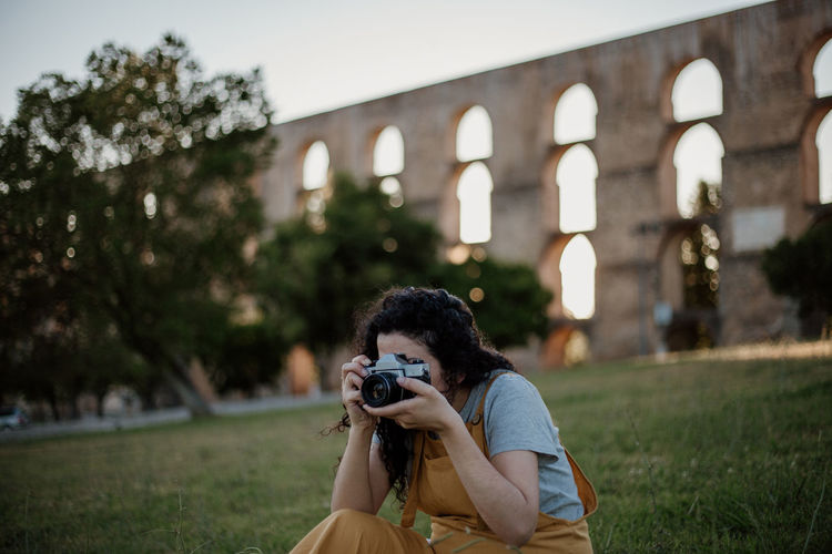 Woman photographing through camera against built structure