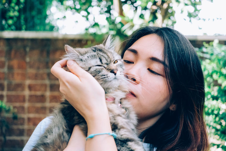 Beautiful young woman with cat with eyes closed