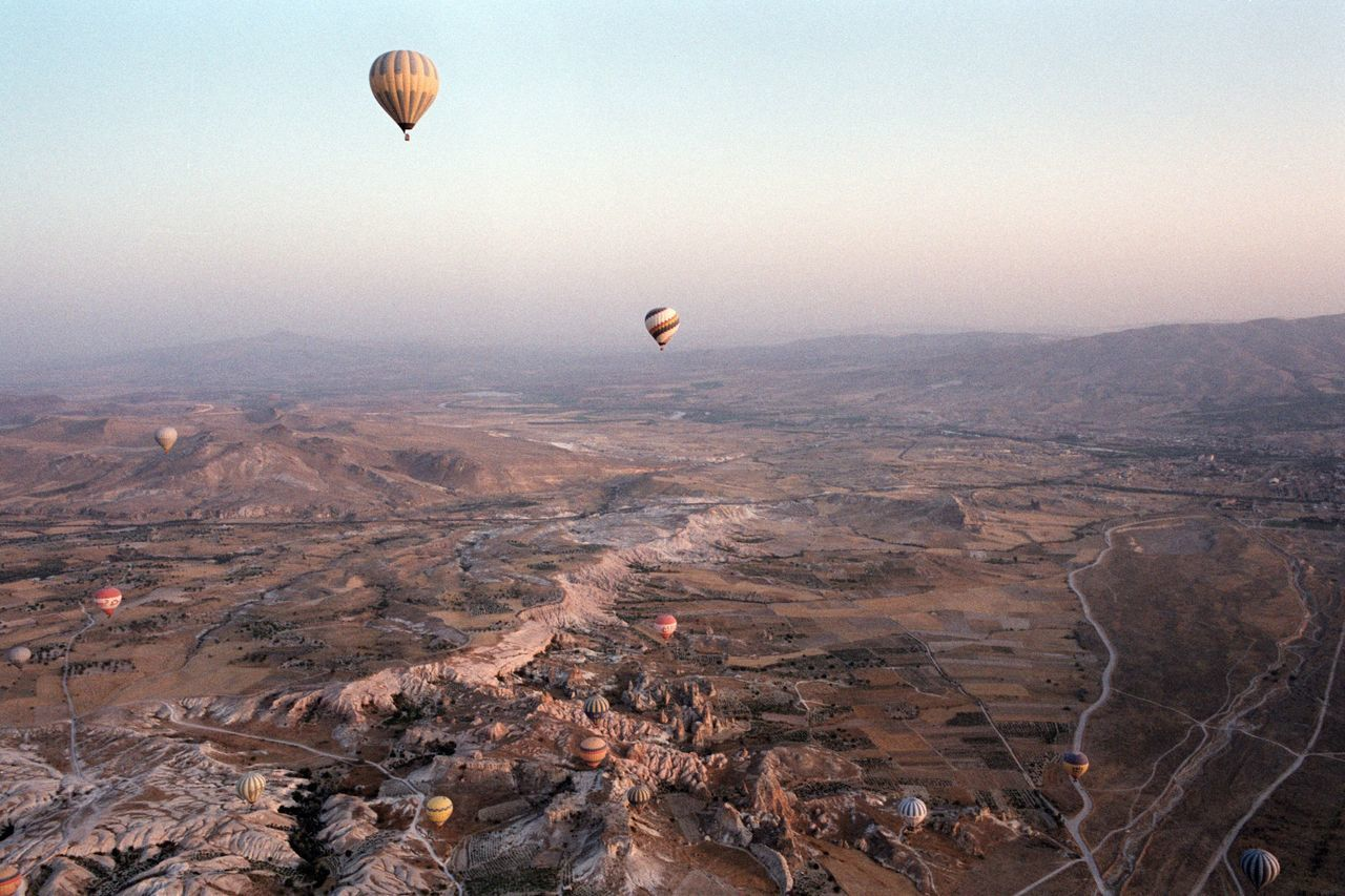 air vehicle, mid-air, balloon, hot air balloon, adventure, flying, transportation, scenics - nature, sky, mountain, landscape, beauty in nature, non-urban scene, environment, nature, travel, day, mode of transportation, tranquil scene, tourism, no people, outdoors, ballooning festival