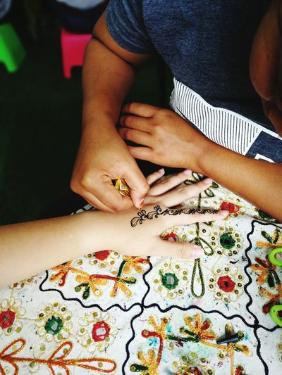 High Angle View Of Female Drawing Henna Tattoo On Woman Hand
