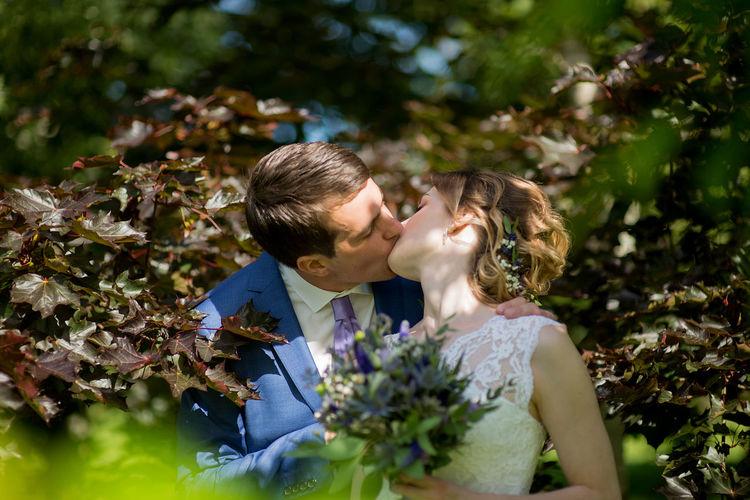 Affectionate wedding couple kissing amidst plants at park
