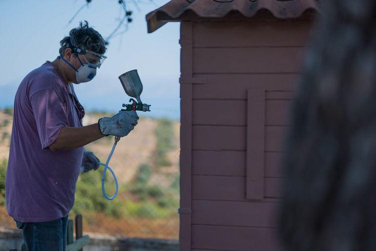 Man spraying paint over log cabin