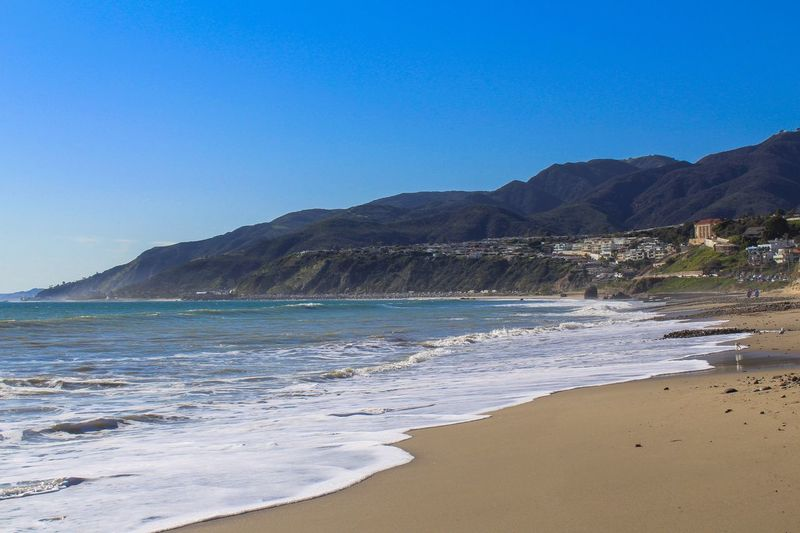 Beach Sea Blue Sand Scenics Nature Beauty In Nature Mountain Outdoors Landscape Travel Destinations Tranquility Water Clear Sky No People Vacations Day Wave Sky