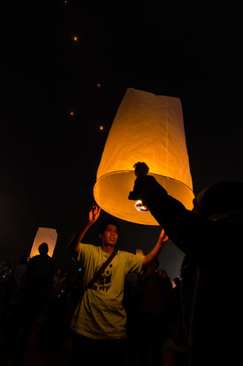 15 may 2014, Magelang, Indonesia : Participants releasing lanterns over the Borobudur temple in Magelang, Central Java during Vesak/Waisak Day celebrations. Adult Arms Raised Celebration Group Of People Human Arm Illuminated Lantern Leisure Activity Lifestyles Lighting Equipment Men Night Orange Color Paper Lantern People Real People Togetherness Traditional Festival Women Yellow