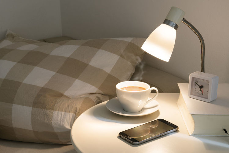 bedside table with fresh coffee, alarm clock, phone and book, concept for a good sleep and a rested wake up in the morning Bed Coffee Home Morning Nightstand Pillow Alarm Clock Bedroom Bedside  Biorhythm Book Cup Early Furniture Home Interior Indoors  Lamp Late Night No People Sleep Smart Phone Table Time Wake Up