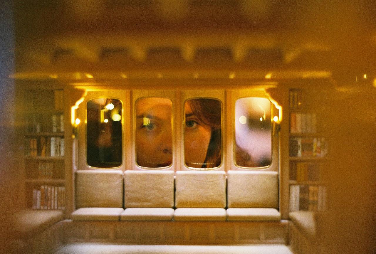 Portrait of woman looking through illuminated window