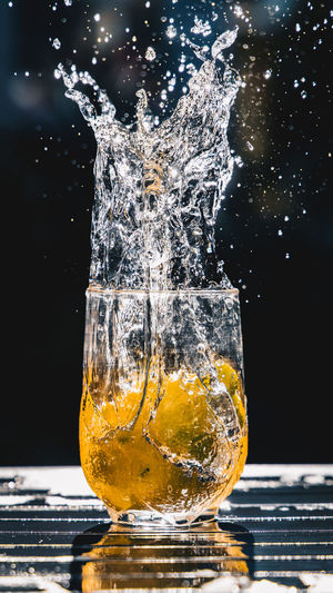 Close-up of glass splashing on table against black background