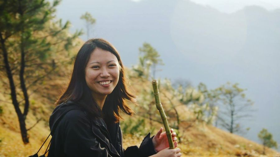 Portrait Of Young Woman Holding Bamboo Outdoors