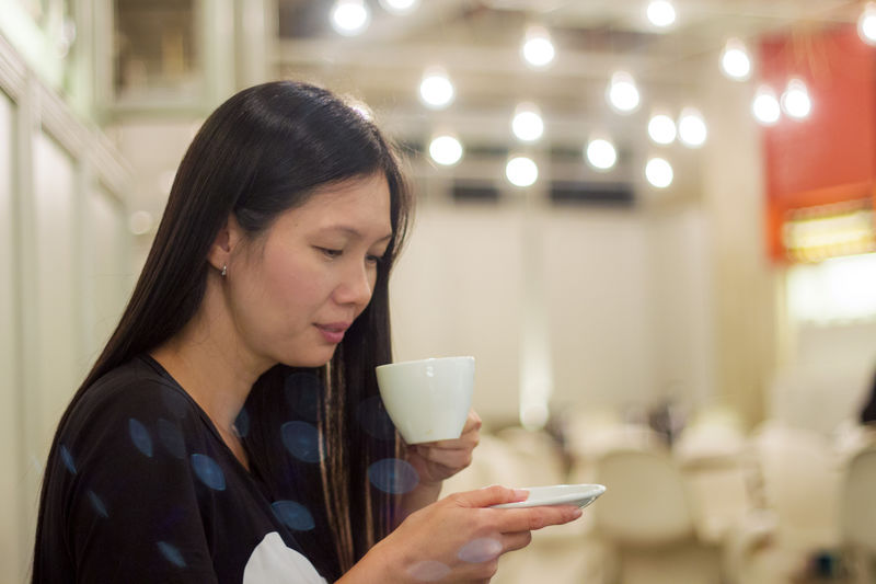 Close-Up Of Smiling Woman Looking Down While Having Coffee At Restaurant