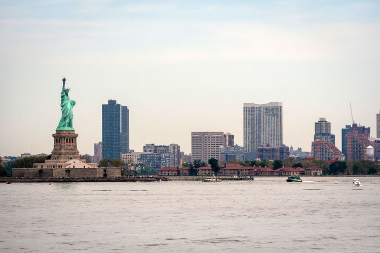 New York, USA - June 7, 2019: Ferry Boat approaching the Statue of Liberty, Liberty Island - Image Liberty Statue Ferry Manhattan USA Tourism City Freedom Boat River Travel Landmark America Sky Island Water NYC Downtown York Skyscraper Hudson Skyline Cityscape New United Urban American Building Architecture Transportation Blue Monument State Tourist Staten Torch View Metropolitan History Icon Symbol Attraction Ship Metropolis Modern Harbor Day Cruise New York Scenic Built Structure Travel Destinations Sculpture Building Exterior Human Representation Representation Waterfront Nature Female Likeness Office Building Exterior Tall - High No People Outdoors Financial District