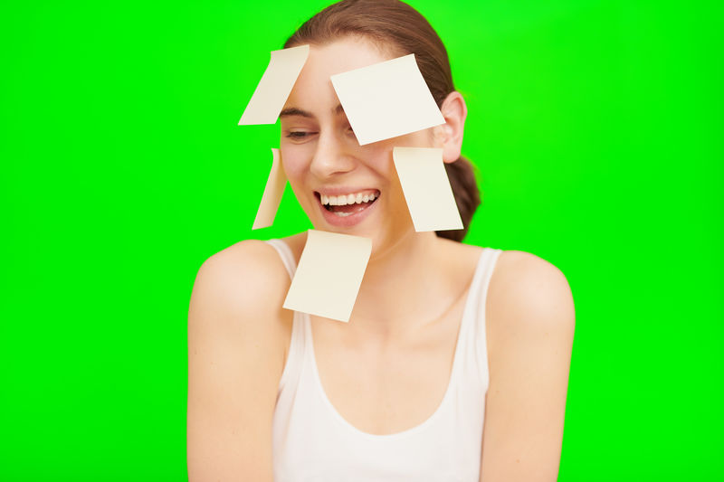 Young woman with notes on her head in front of green is smiling Studio Shot One Person Front View Colored Background Indoors  Green Color Young Adult Portrait Smiling Cut Out Headshot Happiness Women Green Background Standing Looking At Camera Copy Space Emotion Tank Top Beautiful Woman Hairstyle Blank Woman Woman Portrait Young Women Young Girl Female Female Model Thinking Thoughts Happiness Happy Laughing Laugh