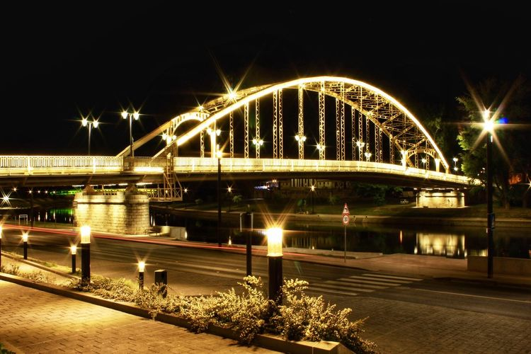 Illuminated bridge over city against sky at night