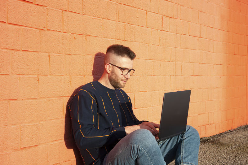 Man using laptop while sitting against brick wall