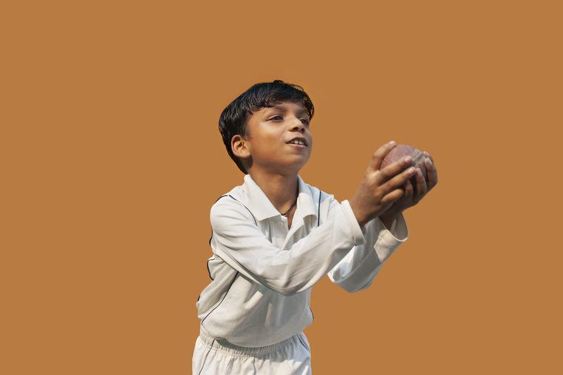 Boy looking away against orange background