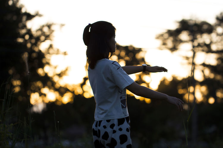 Young woman exercising against silhouette trees during sunrise