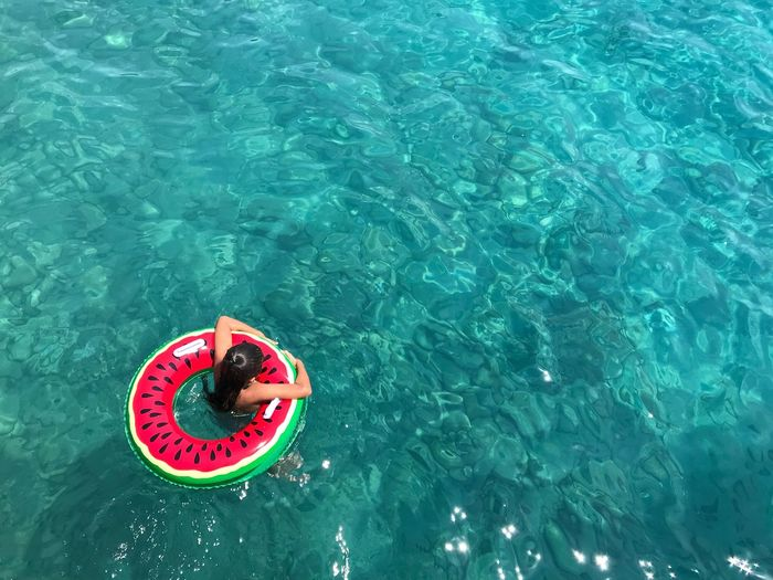 High angle view of girl with inflatable ring swimming in sea