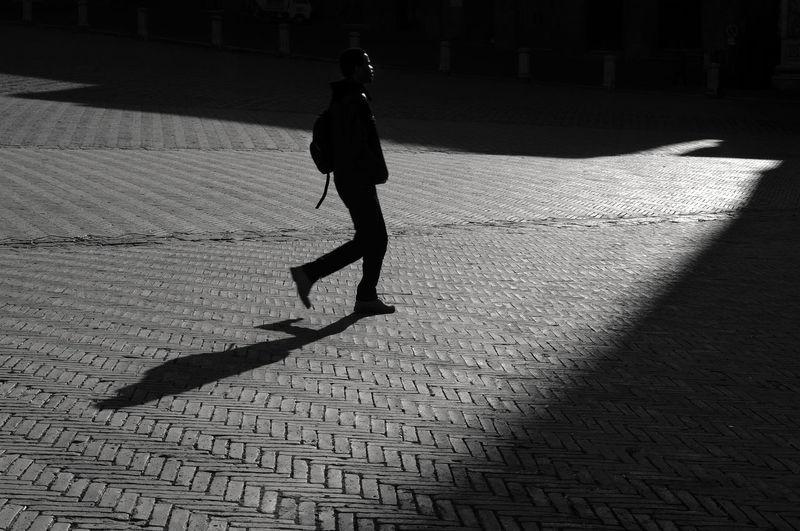 Side View Of Man Walking On Cobblestone Street