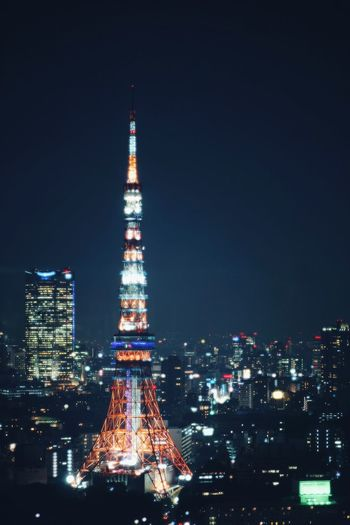 Illuminated tokyo tower amidst buildings in city at night