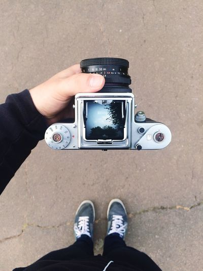 High angle view of man holding camera with reflection of tree in