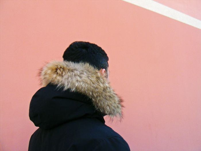 Man Wearing Fur Coat Against Wall During Winter