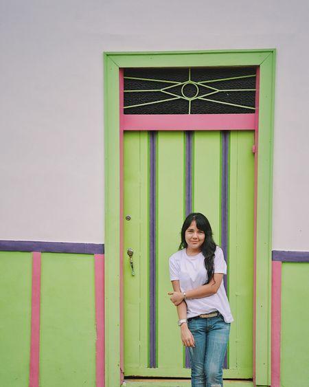 Woman standing against green door