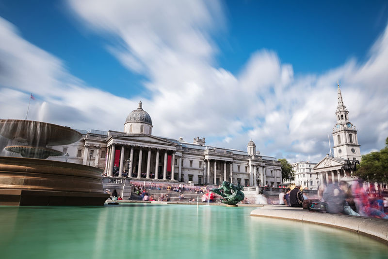 Tourists and locals gather at the main entrance to the national gallery in trafalgar square.